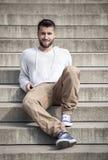Το ελκυστικό άτομο με τη γενειάδα κάθεται στα βήματα Στοκ εικόνα με δικαίωμα ελεύθερης χρήσης
