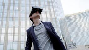 Το ελκυστικό άτομο χρησιμοποιεί τα γυαλιά εικονικής πραγματικότητας στο αστικό διάστημα φιλμ μικρού μήκους