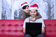 Το ελκυστικό ζεύγος πληρώνει on-line στην ημέρα Χριστουγέννων Στοκ Φωτογραφία