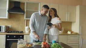 Το ελκυστικό ζεύγος συναντιέται στα ξημερώματα κουζινών Όμορφη γυναίκα που χρησιμοποιεί την ταμπλέτα που μοιράζεται τα κοινωνικά  φιλμ μικρού μήκους