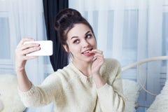 Το ελκυστικό κορίτσι δαγκώνει το δάχτυλό της και τη λήψη selfie Στοκ Φωτογραφία