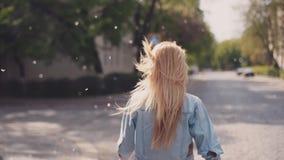 Το ελκυστικό κορίτσι αναρωτιέται κάτω από τις οδούς, γυρίζει στη κάμερα και τα χαμόγελα, θυελλώδης καιρός, tree's άνθος πέφτουν απόθεμα βίντεο