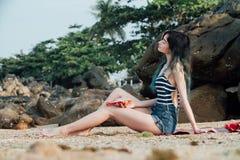 Το ελκυστικό κορίτσι βρίσκεται κάνοντας ηλιοθεραπεία σε μια αμμώδη παραλία με φρούτα δράκων στο χέρι της Στοκ φωτογραφία με δικαίωμα ελεύθερης χρήσης
