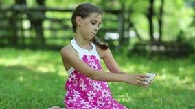 Το ελκυστικό κορίτσι κάθεται στη χλόη και κάνει τις φωτογραφίες στο smartphone του απόθεμα βίντεο