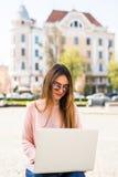 Το ελκυστικό κορίτσι κάνει το πανεπιστημιακό πρόγραμμά της για ένα lap-top έξω μια ηλιόλουστη ημέρα Φορά τα περιστασιακά ενδύματα Στοκ Φωτογραφίες