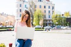 Το ελκυστικό κορίτσι κάνει το πανεπιστημιακό πρόγραμμά της για ένα lap-top έξω μια ηλιόλουστη ημέρα Φορά τα περιστασιακά ενδύματα Στοκ φωτογραφίες με δικαίωμα ελεύθερης χρήσης