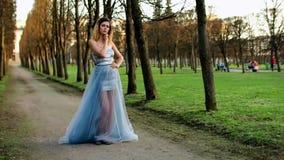 Το ελκυστικό κορίτσι με τα μαύρα brows και τη σγουρή τρίχα στο ασημένιο και μπλε φόρεμα θέτει τη στάση στην πορεία του χώρου στάθ απόθεμα βίντεο
