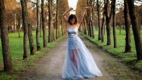 Το ελκυστικό κορίτσι με τα μαύρα brows και τη σγουρή τρίχα στο ασημένιο και μπλε φόρεμα ρυθμίζει το φόρεμά της και θέτει τη στάση φιλμ μικρού μήκους