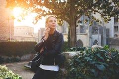 Το ελκυστικό κορίτσι hipster μιλά στο κινητό τηλέφωνο με το φίλο της κατά τη διάρκεια του χρόνου αναψυχής στοκ εικόνα