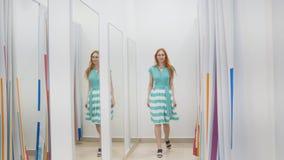 Το ελκυστικό κόκκινο κορίτσι τρίχας επιλέγει το πράσινο φόρεμα κοντά στον καθρέφτη στο δωμάτιο συναρμολογήσεων στο κατάστημα Στοκ Φωτογραφίες