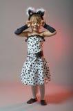 Το ελκυστικό μικρό κορίτσι έντυσε ως γάτα σε ένα γκρίζο υπόβαθρο Στοκ Φωτογραφία