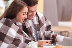 Το ελκυστικό νέο αγαπώντας ζεύγος στηρίζεται στον καφέ Στοκ Φωτογραφίες