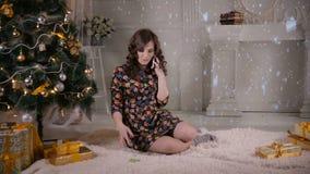 Το ελκυστικό νέο κορίτσι μιλά με κινητό τηλέφωνο κοντά στο χριστουγεννιάτικο δέντρο γιορτάστε τη φθορά santa μητέρων καπέλων κορώ απόθεμα βίντεο