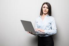 Το ελκυστικό νέο κορίτσι στα περιστασιακά ενδύματα κρατά ένα lap-top, εξετάζει τη κάμερα και χαμογελά, στο γκρίζο υπόβαθρο Στοκ εικόνες με δικαίωμα ελεύθερης χρήσης