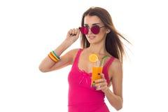 Το ελκυστικό νέο κορίτσι στο ρόδινο πουκάμισο και τα γυαλιά ηλίου πίνουν το πορτοκαλί κοκτέιλ που απομονώνεται στο άσπρο υπόβαθρο Στοκ φωτογραφία με δικαίωμα ελεύθερης χρήσης