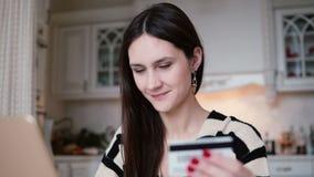 Το ελκυστικό νέο χαμογελώντας Ομάν χρησιμοποιεί την πλαστική πιστωτική κάρτα ψωνίζοντας on-line με το lap-top Αργές κινήσεις καμε απόθεμα βίντεο