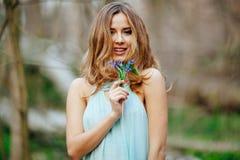 Το ελκυστικό πρότυπο στην μπλε μυρωδιά φορεμάτων snowdrop ανθίζει την άνοιξη το δάσος στοκ φωτογραφία