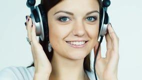 Το ελκυστικό σκοτεινός-μαλλιαρό κορίτσι βάζει στα ακουστικά και το άκουσμα στη μουσική φιλμ μικρού μήκους