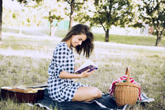 Το ελκυστικό brunette χαμογελά διαβάζοντας το βιβλίο Στοκ φωτογραφία με δικαίωμα ελεύθερης χρήσης