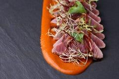 Το ζαμπόν με το arugula, και η σάλτσα καρότων στο σκοτεινό υπόβαθρο Στοκ φωτογραφία με δικαίωμα ελεύθερης χρήσης