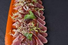 Το ζαμπόν με το arugula, και η σάλτσα καρότων στο σκοτεινό υπόβαθρο Στοκ Εικόνες