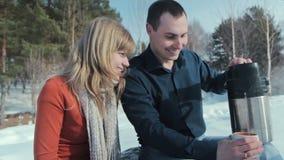το ζευγάρι ατόμων χύνει στα thermos τσαγιού τις ξύλινες νεολαίες Το άτομο χύνει στο τσάι από τα thermos απόθεμα βίντεο