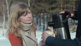 το ζευγάρι ατόμων χύνει στα thermos τσαγιού τις ξύλινες νεολαίες Το άτομο χύνει στο τσάι από τα thermos φιλμ μικρού μήκους
