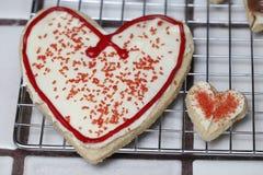 Το ζευγάρι σχέσης των μπισκότων ζάχαρης καρδιών με το άσπρα πάγωμα και το κόκκινο ψεκάζει αντιπροσώπευση της σχέσης Στοκ φωτογραφία με δικαίωμα ελεύθερης χρήσης