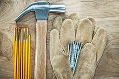 Το ζευγάρι της ασφάλειας φορά γάντια στα ξύλινα καρφιά σφυριών νυχιών μετρητών ξύλινο boa Στοκ Φωτογραφία