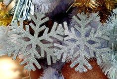 Το ζευγάρι του ασημιού ακτινοβολεί διαμορφωμένη Snowflake διακόσμηση Χριστουγέννων στο χριστουγεννιάτικο δέντρο Στοκ εικόνα με δικαίωμα ελεύθερης χρήσης
