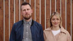 Το ζευγάρι του νεαρού άνδρα και η γυναίκα στέκονται ήρεμα στην οδό και εξετάζουν τη κάμερα απόθεμα βίντεο