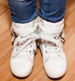 Το ζευγάρι των άσπρων παπουτσιών δέρματος με τις δαντέλλες εσύνδεσε στο λ του κοριτσιού Στοκ Φωτογραφία