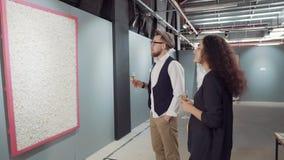 Το ζευγάρι των ειδημόντων της σύγχρονης τέχνης βλέπει τον καμβά με την αφηρημένη εικόνα απόθεμα βίντεο