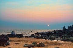 Το ζευγάρι των εραστών κάθεται στις πέτρες στην παραλία στο ηλιοβασίλεμα Στοκ Φωτογραφίες