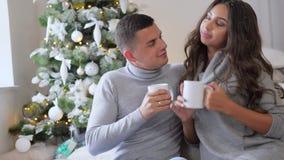 Το ζευγάρι των εραστών που χαμογελούν και πίνει τον καφέ στον εγχώριο καναπέ του το πρωί στο υπόβαθρο του διακοσμημένου χριστουγε φιλμ μικρού μήκους