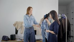 Το ζευγάρι των θηλυκών φίλων βλέπει τα ενδύματα στο σπίτι μαζί, το κοίταγμα στα τζιν και το γέλιο, ταξινομώντας την ντουλάπα απόθεμα βίντεο