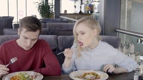 Το ζευγάρι των συναδέλφων τρώει τη σαλάτα άνετο σε restaurent, σε αργή κίνηση φιλμ μικρού μήκους