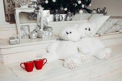 Το ζεύγος δύο άσπρου teddy αντέχει τα παιχνίδια καθμένος κοντά σε χριστουγεννιάτικο δέντρο και δύο κόκκινα φλιτζάνια του καφέ στοκ εικόνες