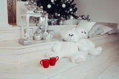 Το ζεύγος δύο άσπρου teddy αντέχει τα παιχνίδια καθμένος κοντά σε χριστουγεννιάτικο δέντρο και δύο κόκκινα φλιτζάνια του καφέ στοκ εικόνες με δικαίωμα ελεύθερης χρήσης