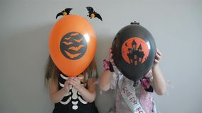 Το ζεύγος δύο χαμογελώντας μικρών κοριτσιών έντυσε στα κοστούμια αποκριών κρατώντας τα μπαλόνια και την τοποθέτηση αέρα απόθεμα βίντεο