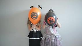 Το ζεύγος δύο χαμογελώντας μικρών κοριτσιών έντυσε στα μπαλόνια και την τοποθέτηση αέρα εκμετάλλευσης κοστουμιών αποκριών απόθεμα βίντεο