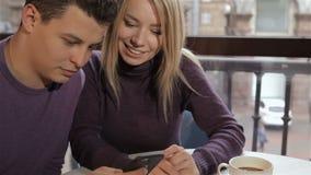 Το ζεύγος εξετάζει τον ανθρώπινο καφέ smartphone απόθεμα βίντεο