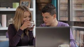 Το ζεύγος εξετάζει το lap-top στον καφέ απόθεμα βίντεο