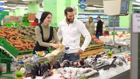 Το ζεύγος επιλέγει τα ψάρια και χαμογελά κάνοντας τις αγορές στην υπεραγορά απόθεμα βίντεο