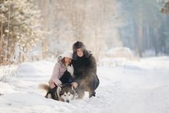 Το ζεύγος εραστών περπατά στο χιόνι με το σκυλί στοκ εικόνες