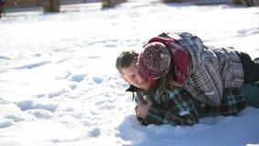Το ζεύγος ερωτευμένο φιλά να βρεθεί στο χιόνι κατά τη διάρκεια της ηλιόλουστης θερμής χειμερινής ημέρας Ο όμορφος άνδρας και η όμ φιλμ μικρού μήκους