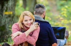 Το ζεύγος ερωτευμένο χαλαρώνει στο δάσος φθινοπώρου με το lap-top   ευτυχές καφές ή κρασί ποτών κοριτσιών καυτό το άτομο κάθεται  στοκ φωτογραφία