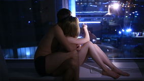 Το ζεύγος η συνεδρίαση ανδρών και γυναικών από το παράθυρο τη νύχτα και εξετάζοντας την πόλη νύχτας απόθεμα βίντεο