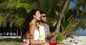 Το ζεύγος κάθεται το αγκάλιασμα στην παραλία κάτω από τους φοίνικες χρησιμοποιώντας το έξυπνο τηλέφωνο κυττάρων, τον ευτυχή χαμογ απόθεμα βίντεο