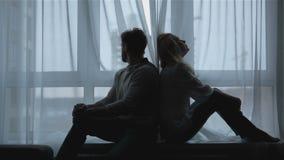 Το ζεύγος κάθεται πλάτη με πλάτη στο σπίτι απόθεμα βίντεο